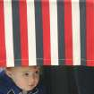 Chandler Lorimer, 2, Galena, peeks out under the voting curtain while at Galena City Hall in Galena, Kan., while his mother Jamie votes on Tuesday, Nov. 6, 2012. (AP Photo/The Joplin Globe, Roger Nomer)
