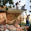 Bricks from a toppled chimney cover the ground next to the Reneau home as friends work on the roof to place a large top over the opening created when the chimney collapsed onto the roof. An earthquake late Saturday night caused extensive damage to the two-story ranch style home of Joseph and Mary Reneau near the community of Sparks in Lincoln County.  Contents inside their home were damaged earlier Saturday when a earthquake was struck the same area.  The Reneaus have lived in their house for 25 years. Photo by Jim Beckel, The Oklahoman  ORG XMIT: KOD