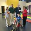 Vivian Gibson (right), a trustee of the Oklahoma Electric Cooperative Foundation, presents a check to Jim Ballard, vice president of the Sooner AMBUCS in Norman. The check for $3,752.75 is a grant to Sooner AMBUCS to purchase four of the latest models of the AMBUCS AMTRYKE. The grant presentation was made in the therapy gym of the J. D. McCarty Center in Norman. The McCarty Center is the AMTRYKE demonstration site for this area of Oklahoma. Also present were Kari Dahlke, certified occupational therapy assistant at the McCarty Center, Uwe von Schamann, director of development for the McCarty Center, and demonstrating a new model AMTRYKE is McCarty Center patient Nathan Landry.  Community Photo By:  Greg Gaston  Submitted By:  Greg,