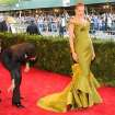Designer Zac Posen, left, fixes the dress of actress Uma Thurman as they attend The Metropolitan Museum of Art's Costume Institute benefit celebrating
