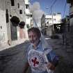 A International Red Cross employee runs for cover after an Israeli strike during a two-hour temporary ceasefire in Gaza City's Shijaiyah neighborhood, Wednesday, July 23, 2014. Israeli troops battled Hamas militants on Wednesday near a southern Gaza Strip town as U.S. Secretary of State John Kerry reported progress in efforts to broker a truce in a war that has so far killed more than 650 Palestinians and at least 30 Israelis. (AP Photo/Khalil Hamra)