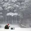 A Belarusian fisherman sits on the frozen lake during snowfall on the outskirts of the capital Minsk, Belarus, Thursday, Jan. 17, 2013. The heavy snowfall across Belarus began last night. (AP Photo/Sergei Grits)