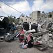 Palestinian family members rest by the rubble of their destroyed house during a 12-hour cease-fire in Gaza City's Shijaiyah neighborhood, Saturday, July 26, 2014. Gaza residents used a 12-hour humanitarian cease-fire on Saturday to stock up on supplies and survey the devastation from nearly three weeks of fighting, as they braced for a resumption of Israel's war on Hamas amid stalled efforts to secure a longer truce. (AP Photo/Khalil Hamra)