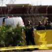 Arizona officials check a body found in bushes by a landscaper in the Phoenix suburb of Mesa, Arizona on Thursday, Jan. 31, 2013.   A body matching Arthur Harmon's description was found nearby with an apparent self-inflicted gunshot wound, spokesman Sgt. Steve Martos said. Harmon is a  suspect in a mass shooting that killed a man and critically wounded another. (AP Photo/Jacques Billeaud)