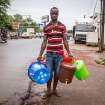 A street trader in Freetown sells plastic hand washing buckets, as demand for basic sanitation products has boomed during the Ebola crisis with a simple bucket and tap selling for around ten dollars in the city of Freetown, Sierra Leone, Wednesday, Aug. 6, 2014. The World Health Organization has begun an emergency meeting on the Ebola crisis, and said at least 932 deaths in four African countries are blamed on the virus, with many hundreds more being treated in quarantine conditions. (AP Photo/ Michael Duff)