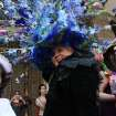 Vanessa Sterbenz-Guerra, of the Queens borough of New York, foreground wearing black, smiles as she poses for photographs with a flowery hat atop her head as she and others take part in the Easter Parade along New York's Fifth Avenue Sunday April 24, 2011. (AP Photo/Tina Fineberg)