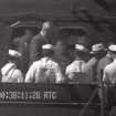 This image from an eight-second film clip provided by the National Archives shows President Franklin Delano Roosevelt, third from right, being pushed in a wheelchair aboard the U.S.S. Baltimore in Pearl Harbor in July 1944, depicting a secret not revealed to the public until after his death. (AP Photo/National Archives)