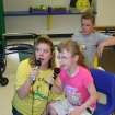 Singing karaoke was one activity used to build confidence and self-esteem among campers who attended the friendship session of Camp ClapHans summer day camp at the J. D. McCarty Center. Singing a duet is (left) Chrissy Hancock, McCarty Center speech-language pathologist and friendship camp session director, and camper Ginney Webb of Lexington. Listening in the background is camper Chase Hoover from Midwest City.  Community Photo By:  Greg Gaston  Submitted By:  Greg,