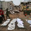 Stretchers with a body bags are placed on standby while workers toil in the collapsed garment factory building,  Tuesday, April 30, 2013 in Savar, near Dhaka, Bangladesh. Emergency workers hauling large concrete slabs from a collapsed 8-story building said Tuesday they expect to find many dead bodies when they reach the ground floor, indicating the death toll will be far more than the official 386. One estimate said it could be as high as 1,400. The illegally constructed, 8-story Rana Plaza collapsed on the morning of April 24, bringing down the five garment factories inside.(AP Photo/Wong Maye-E)