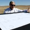 In this March 13, 2012 photo, Rob Burpo, president of First American Financial Advisors Inc., looks at a map of a planned 30-megawatt solar photovoltaic plant near the Navajo community of To'Hajiilee, N.M. Once constructed, the plant stands to be the largest photovoltaic array on tribal land in the U.S. (AP Photo/Susan Montoya Bryan)