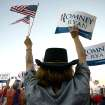 Darlene Egtvedt, who traveled from West Virginia to see the rally, waves American flags and a sign in support of Republican presidential candidate Mitt Romney and vice-presidential candidate Paul Ryan at a campaign rally at the Augusta County Expoland in Fishersville, Va., on Thursday, Oct. 4, 2012. (AP Photo/The Daily News-Record, Stephen Mitchell)