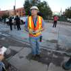 In this photo taken with a fisheye lens, an unidentified worker, center, from the Denver Water Department talks to reporters about a water main break in front of Coors Field that forced the cancellation of the baseball game betwen the Cincinnati Reds and the Colorado Rockies in Denver on Saturday, Aug. 16, 2014. The game will be made up as part of a split doubleheader on Sunday. (AP Photo/David Zalubowski)