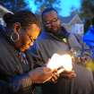 File - In this Nov. 6, 2013 file photo Charles Hannah lights Theresa Walker's candle, left,  at a vigil for Renisha McBride in the front of the home where she was shot in Dearborn Heights, Mich. Prosecutors plan to announce Friday, Nov. 15, 2013 whether they'll  charge a suburban Detroit homeowner in the shooting death of McBride. Autopsy results released after the shooting ruled McBride died of a gunshot wound to her face. (AP Photo/Detroit News, Ricardo Thomas, File)  DETROIT FREE PRESS OUT; HUFFINGTON POST OUT