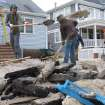 Volunteers shovel sand from the front yard of a home near the ocean in Lavallette N.J.  Friday, Jan. 4, 2013, shortly before Congress voted to approve aid for victims of Superstorm Sandy. Many shore residents were angry that Congress took so long to act after the Oct. 29 storm. (AP Photo/Wayne Parry)