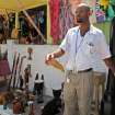 In this Sept. 26, 2012 photo, street vendor Paul Davy sells wooden statues to tourists who disembarked from the Royal Caribbean's Allure of the Seas cruise ship in Falmouth, northern Jamaica. Trade groups say the flourishing cruise ship industry injects about $2 billion a year into the economies of the Caribbean, the world's No. 1 cruise destination, but critics complain that it produces relatively little local revenue because so many passengers dine, shop and purchase heavily marked-up shore excursions on the boats or splurge at international chain shops on the piers. (AP Photo/David McFadden)