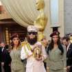 Sacha Baron Cohen, center, smiles after dropping a substance on the red carpet as he arrives before the 84th Academy Awards on Sunday, Feb. 26, 2012, in the Hollywood section of Los Angeles. (AP Photo/Chris Pizzello) ORG XMIT: OSC260