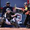 Oklahoma State Cowgirl Chelsea Garcia bunts as Iowa's Liz Watkins watches during the Oklahoma State - Iowa game at