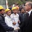 In this photo released by the Turkish Prime Minister's Press Office, Turkish Prime Minister Recep Tayyip Erdogan is surrounded by security members as he visits the coal mine in Soma, Turkey, Wednesday, May 14, 2014.  Nearly 450 miners were rescued, the mining company said, but the fate of an unknown number of others remained unclear as bodies are still being brought to the surface and burials are underway after one of the world's deadliest mining disasters. (AP Photo/Kayhan Ozer, Turkish Prime Minister's Press Office, HO)