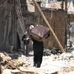 In this Saturday April 21, 2012 photo, a Syrian man leaves his home carriying a suitcase as he walks in a destroyed alley damaged from Syrian army forces shelling, at Bab Sbaa neighborhood in Homs province, central Syria. Opposition activists have said observers appear to make a difference in areas where they stay for longer periods, such as the central city of Homs, where a pair of monitors has been deployed since the weekend. Homs had been hammered by regime artillery for weeks, but shelling stopped after the monitors arrived. Gunfights are still reported in some neighborhoods. (AP Photo)
