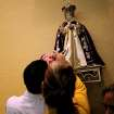 Antonio Aguirre fulfills a promise as he and his family visit the National Shrine Infant Jesus of Prague at St. Wenceslaus Catholic Church in Prague, Oklahoma on Sunday, August 2, 2009. By John Clanton, The Oklahoman