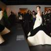 FILE - In this  Feb. 10, 2014 file photo provided by The Metropolitan Museum of Art,  Elettra Wiedemann models a modern day reproduction of a Charles James 1953 Clover Leaf Gown, original shown at left, during a press presentation for the upcoming Costume Institute exhibition,