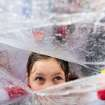 Ten-year-old Tamija looks through a plastic rain cover as she watches the World Cup 2014 soccer match between Germany and United States at a public viewing named 'Fan Mile' in Berlin, Thursday, June 26, 2014.  (AP Photo/Markus Schreiber)