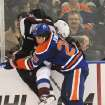 Edmonton Oilers' Ryan Jones, right, checks Colorado Avalanche's Jan Hejda during the second period of an NHL hockey game in Edmonton, Alberta, on Friday, Dec. 9, 2011. (AP Photo/The Canadian Press, John Ulan)