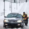 Greensboro police officer A.R. Schoonmaker pushes a car, which became stuck on a hill along the 600 block of West Market St. during the heavy snow in the downtown area on Wednesday, Feb. 12, 2014, in Greensboro, N.C. (AP Photo/News & Record, Jerry Wolford)