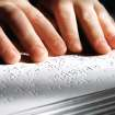 Right: Daniel Brookshire feels Braille letters in his Bible. photo BY JIM BECKEL,  THE OKLAHOMAN