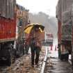An Indian man walks past stranded trucks on the Jammu-Srinagar highway, on the outskirts of Jammu, India, Saturday, Feb. 23, 2013. A fresh spell of rain and snow has blocked the road linking Jammu and Srinagar, the winter and summer capitals respectively of Indian Kashmir. (AP Photo/Channi Anand)
