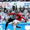 Manchester United's Wayne Rooney, right, vies for the ball with Newcastle United's Cheick Tiote, left,during their English Premier League soccer match at the Sports Direct Arena, Newcastle, England, Sunday, Oct. 7, 2012. (AP Photo/Scott Heppell)