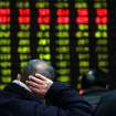 In this photo released by China's Xinhua News Agency, an investor supports his head with a hand while looking at an electric stock price display at a trading hall in a securities firm in Shanghai, China, as the Shanghai Composite Index plummeted 3 percent to 2,325.95 Thursday, Feb. 21, 2013. It was the index's biggest loss in almost 15 months. World stock markets tumbled Thursday after U.S. Federal Reserve minutes gave investors an unwelcome reminder that super-easy monetary policy has an expiration date. (AP Photo/Xinhua, Ding Ding) NO SALES