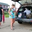 Nicole Specht, and and Ryan Witman, pack their Honda CRV heading back home to Lancaster Pa., before dawn on Thursday, July 3, 2014, during a mandatory evacuation, in Rodanthe, N.C. Arthur strengthened to a hurricane early Thursday and threatened to give North Carolina a glancing blow on Independence Day, prompting a stream of vacationers and residents to head home from some parts of the state's popular but flood-prone Outer Banks. (AP Photo/Jerome Bailey Jr.)