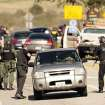 Police stand at a road block at Hwy. 38 and Bryant Street just north of Yucaipa, Calif. as a gunfight between police and fugitive ex-Los Angeles cop Christopher Dorner takes place farther up the highway in the Seven Oaks community, Tuesday, Feb. 12, 2013. (AP Photo/The Press-Enterprise, Stan Lim)  NO SALES; MAGS OUT; MANDATORY CREDIT