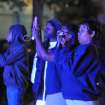 The flashing blue lights of nearby police cars light onlookers trying to capture the scene where authorities say a small plane carrying three people crashed into a home in Jackson, Miss. shortly after 5 p.m. Tuesday evening, Nov. 13, 2012. (AP Photo/The Clarion-Ledger, Joe Ellis) NO SALES