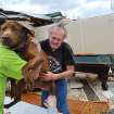 Greg Cook hands his dog Coco to Donnie Watts inside the destroyed home in Limestone County, Ala.  on Friday, March 2, 2012.  A reported tornado destroyed several houses in northern Alabama as storms threatened more twisters across the region Friday (AP Photo/The Decatur Daily, Gary Cosby Jr.) ORG XMIT: ALDEC101