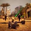 In this Monday, Jan. 28, 2013 photo, an Egyptian protester takes a break while others use green laser pointers during clashes between protesters and Egyptian security forces in Downtown Cairo, Egypt. On Tuesday, Jan. 29, 2013, Egypt's army chief warned of