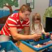 Mustang pre-kindergarten student Cheyanne Fairchild examines shells and other things from a tide pool with the help of Partnership for Academic Student Success student Mark Ray. More than 350 pre-k students took part in Mustang Education Center's first Science Discovery Day.  Community Photo By:  Shannon Rigsby, MPS  Submitted By:  Shannon, Mustang