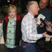 As Phillip Shepard, front, talks to reporters, his wife, Judy, back, tries to slip away from the pack after the couple met with Brooklyn Nets center Jason Collins following the Nets' 112-89 victory over the Denver Nuggets in an NBA basketball game in Denver on Thursday, Feb. 27, 2014. The Shepard's son, Matthew, was killed as part of an anti-gay hate crime in Laramie, Wyo., in 1998. (AP Photo/David Zalubowski)