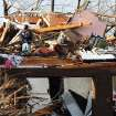 A man inspects the damage at a home in Henryville, Ind.,after powerful storms stretching from the U.S. Gulf Coast to the Great Lakes in the north wrecked two small towns and killed at least eight people Friday, March 2, 2012, as the system tore roofs off schools and homes and damaged a maximum security prison. It was the second deadly tornado outbreak this week. (AP Photo/The News and Tribune, C.E. Branham) ORG XMIT: INJEF102