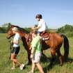 "Camper Mark McBride enjoys his ride on American Quarter Horse King Glo Jessie as one of the many activities of the Movin' & Groovin' summer day camp at the J. D. McCarty Center for children with developmental disabilities in Norman. Leading ""Jessie"" around the pasture is summer day camp volunteer Ashley Birchfield. Acting as one of the side walkers is Jennifer Woodruff, physical therapist and camp director.  Community Photo By:  Greg Gaston  Submitted By:  Greg,"