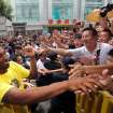 FILE - In this Aug. 16, 2012 file photo, Los Angeles Lakers' Kobe Bryant, left, shakes hands with Chinese fans during a