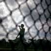 Baltimore Orioles pitcher Tsuyoshi Wada, of Japan, is seen through mesh fencing as he takes a drink of water during a workout as pitchers and catchers report to spring training baseball Saturday, Feb. 18, 2012, in Sarasota, Fla. (AP Photo/David Goldman)