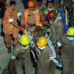 Rescue workers evacuate a burns victim from a fire which broke out in a garment factory building which collapsed Wednesday in Savar, near Dhaka, Bangladesh, Sunday April 28, 2013. A fire broke out late Sunday in the wreckage of the garment factory that collapsed last week in Bangladesh, with smoke pouring from the piles of shattered concrete and some of the rescue efforts forced to stop. The fire came four days after the collapse, as rescuers were trying to free a woman they found trapped in the rubble.(AP Photo/Wong Maye-E)