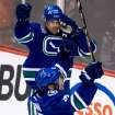 Vancouver Canucks' Henrik Sedin, bottom, of Sweden, celebrates his goal against the San Jose Sharks with his twin brother Daniel Sedin, of Sweden, during the second period of an NHL hockey game in Vancouver, British Columbia, Tuesday, March 5, 2013. (AP Photo/The Canadian Press, Darryl Dyck)