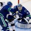 Vancouver Canucks goalie Cory Schneider, right, stops Los Angeles Kings' Dustin Brown as Alexander Edler, of Sweden, defends during the third period of an NHL hockey game in Vancouver, British Columbia on Saturday, March 2, 2013. (AP Photo/The Canadian Press, Darryl Dyck)