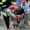 Medical workers aid an injured man at the 2013 Boston Marathon following an explosion in Boston, Monday, April 15, 2013. Two bombs exploded near the finish of the Boston Marathon on Monday, killing at least two people, injuring at least 22 others and sending authorities rushing to aid wounded spectators. (AP Photo/The Boston Globe, David L. Ryan) MANDATORY CREDIT ORG XMIT: MABOD901