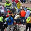 Medical workers aid injured people at the 2013 Boston Marathon following an explosion in Boston, Monday, April 15, 2013. Two explosions shattered the euphoria of the Boston Marathon finish line on Monday, sending authorities out on the course to carry off the injured while the stragglers were rerouted away from the smoking site of the blasts. (AP Photo/The Boston Globe, David L Ryan)  MANDATORY CREDIT ORG XMIT: MABOD807