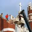 An eathquake late Saturday night caused extensive damage to the towers (turrets) atop Benedictine Hall, the most prominent structure on the campus of St. Gregory's University in Shawnee.  Crews from the university's maintenance department used a large crane on  Sunday afternoon, Nov. 6, 2011, to remove loosened bricks and  place a large top over the southwest tower's opening.  Photo by Jim Beckel, The Oklahoman  ORG XMIT: KOD