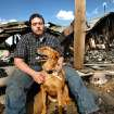 Walt Harmon, 24, sits with his dog, Pal, a mutt, at the back of what's left of his family's home Tuesday afternoon, July 19, 2011. The dog awakened Walt's mother,  Susan Harmon with constant barking Sunday night when their home caught fire. Walt credits the pet with saving his life and allowing him to rescue his mother, and her parents, Harold and Donna Gilliam.  from the smoke-filled home before it was destroyed by flames.   The home is in rural Lincoln County about six miles north of Jacktown.     Photo by Jim Beckel, The Oklahoman